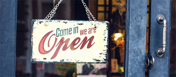 photograph of a sign on a business that reads Come in. We are open.
